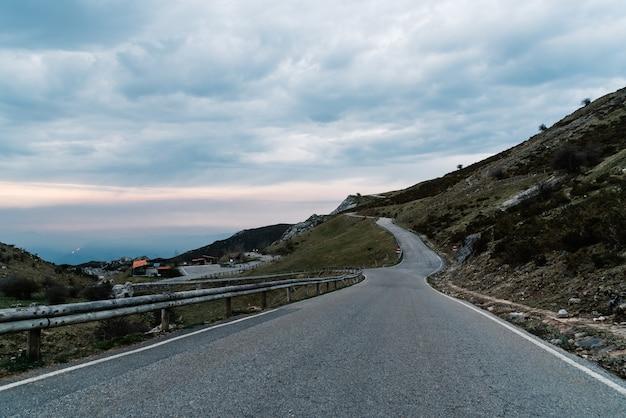 Route Entourée De Montagnes Sous Un Ciel Nuageux Le Soir Photo gratuit