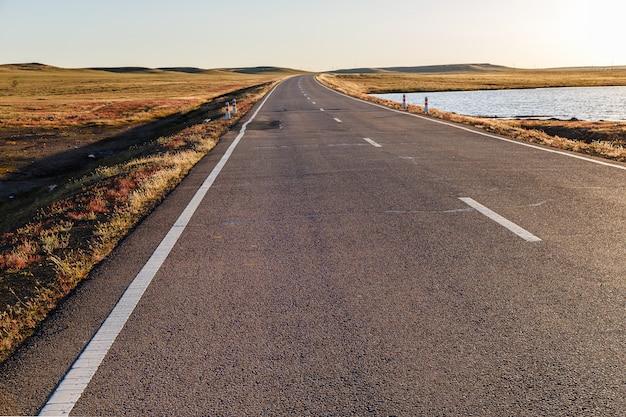 Route goudronnée dans la steppe mongole au bord d'un petit lac Photo Premium