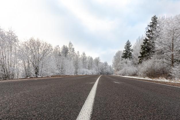 Route D'hiver Au Jour De Gel Avec Ciel Bleu, Paysage Avec Des Arbres Couverts De Neige, Motif De Bande De Séparation De Route Blanche Et De Glace Sur L'asphalte Photo Premium