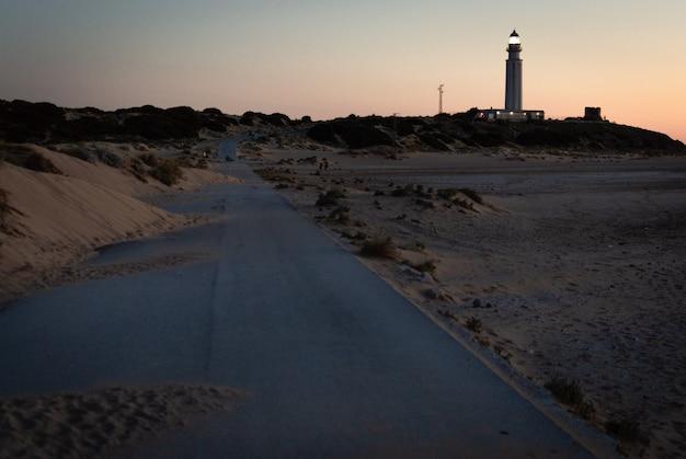 Route recouverte de sable des dunes, route vers le phare de trafalgar, cadix, espagne au coucher du soleil Photo Premium