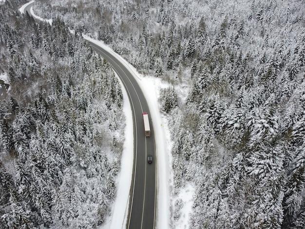 Route Sinueuse à Travers Les Bois En Hiver. Asphalte à Travers Le Col Jusqu'au Sommet De La Montagne En Roumanie Photo Premium