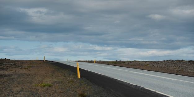 Route stérile disparaissant à l'horizon sous un ciel nuageux Photo Premium