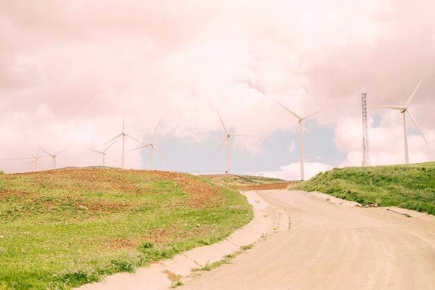 Route à travers les champs avec des moulins à vent Photo gratuit