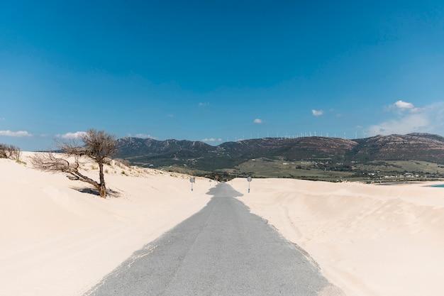 Route vide dans le sable contre les montagnes Photo gratuit