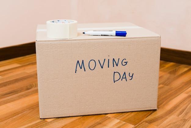 Ruban adhésif et marqueur sur la boîte en carton du jour du déménagement, sur le plancher de bois franc Photo gratuit