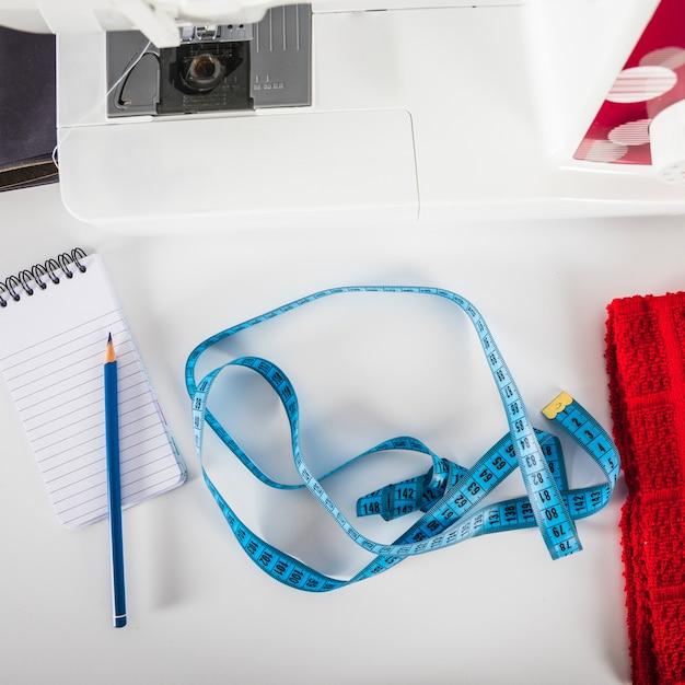 Ruban à mesurer et cahier près de la machine à coudre Photo gratuit