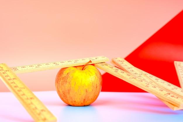 Ruban à mesurer à côté d'une pomme, concept de perte de poids avec une alimentation saine. Photo Premium