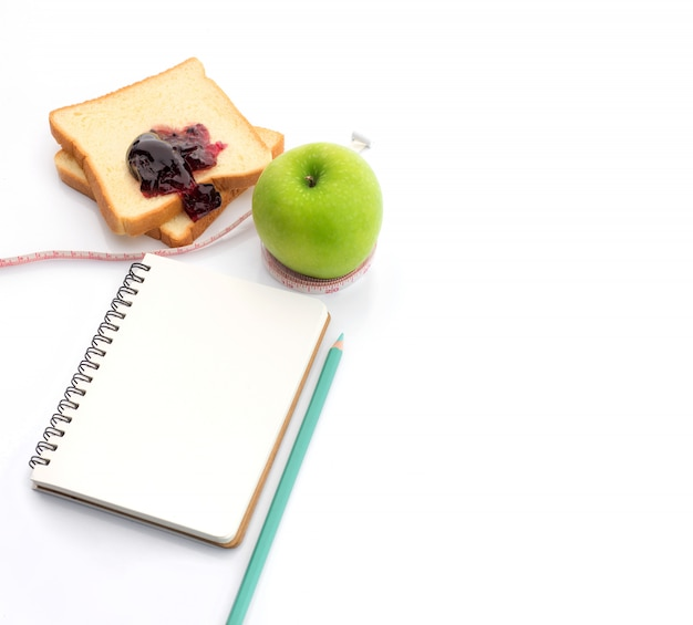 Ruban à mesurer enroulé autour d'une pomme verte avec slice Photo Premium