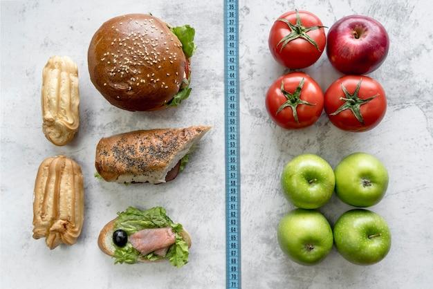 Ruban à mesurer entre aliments sains et malsains sur fond de béton Photo gratuit