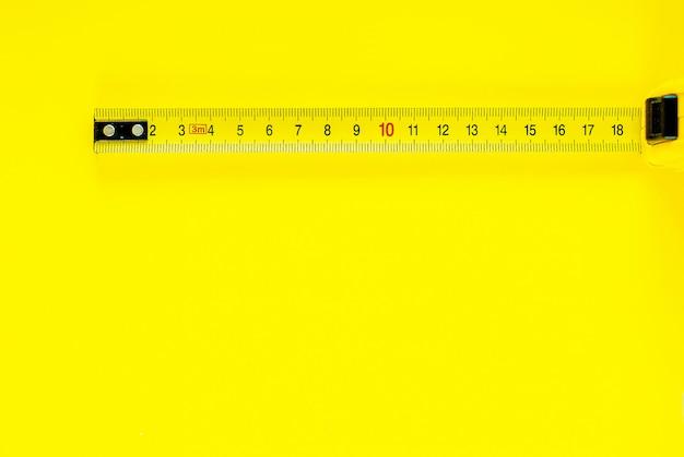 Ruban à mesurer jaune sur fond jaune. espace de copie Photo Premium