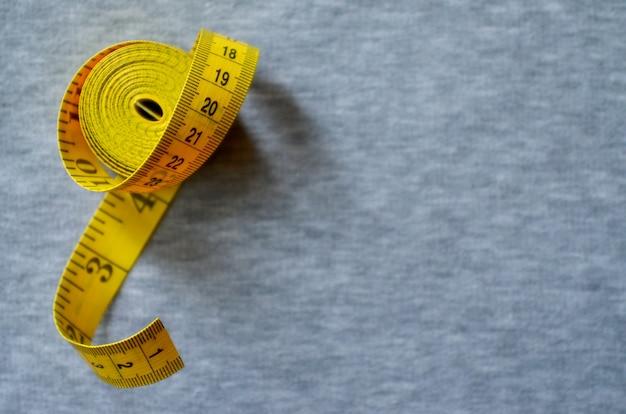 Ruban à mesurer jaune se trouve sur un tricot gris Photo Premium