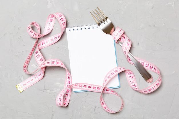 Ruban à mesurer rose, cahier ouvert et fourchette Photo Premium
