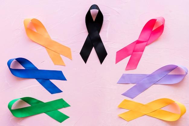 Ruban de sensibilisation coloré divers sur fond rose Photo gratuit