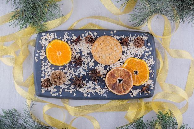 Rubans Autour D'un Plateau De Tranches D'orange, De Biscuits Et De Cônes De Conifères Sur Fond Blanc. Photo gratuit
