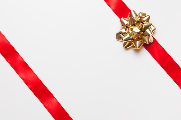Rubans rouges avec noeud doré sur table Photo gratuit