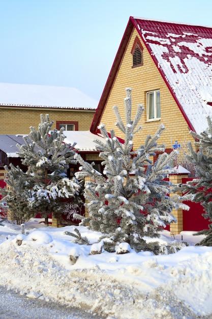 Rue confortable avec des maisons de briques en hiver avec des arbres enneigés Photo Premium