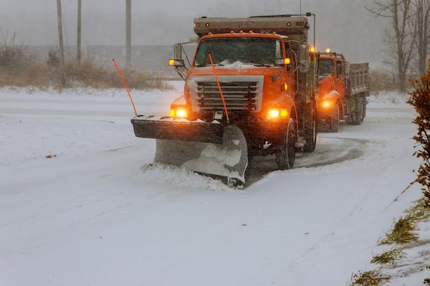 La rue de la neige de gros tracteur pendant le blizzard de neige Photo Premium