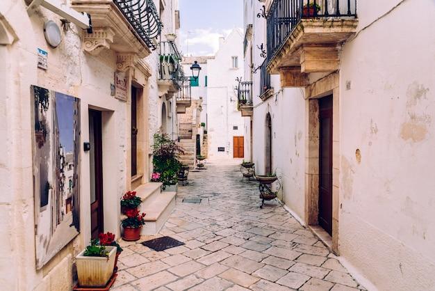 Rues avec des maisons aux murs blanchis à la chaux de la ville italienne typique de locorotondo. Photo Premium