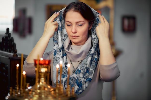 Russe belle femme caucasienne aux cheveux rouges et une écharpe sur la tête est dans l'église orthodoxe Photo Premium