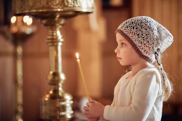 Russe petite fille dans un foulard sur la tête se dresse dans une église orthodoxe Photo Premium