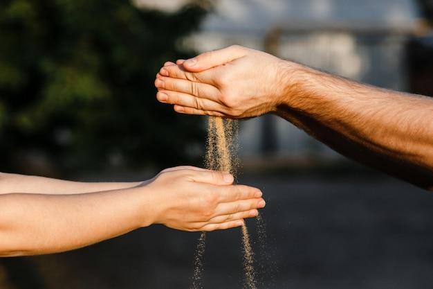 Le Sable Est Versé Des Mains Des Hommes Aux Mains Des Femmes. Photo Premium