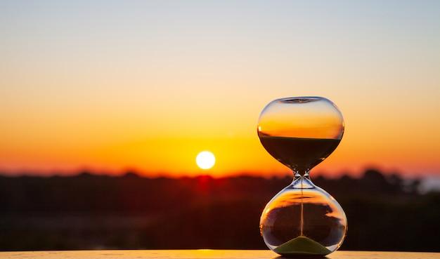 Sablier Au Coucher Du Soleil Ou à L'aube Sur Un Arrière-plan Flou, Pour Rappeler Le Temps Qui Passe Photo Premium