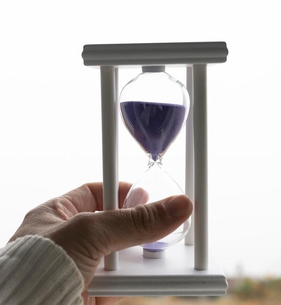 Un Sablier Blanc Avec Du Sable Violet Photo Premium