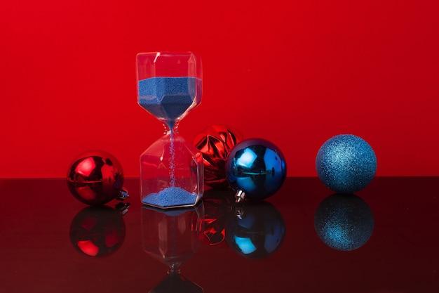 Sablier Et Boules De Noël Contre Rouge Photo Premium