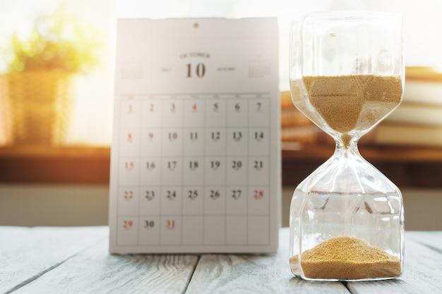 Sablier Avec Calendrier Sur Un Bureau En Bois Se Bouchent. Concept De Temps Photo Premium