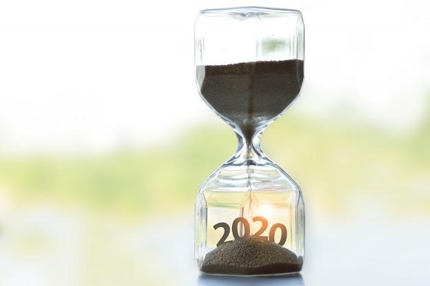 Le Sablier Posé Sur La Table Indique Que La Période De L'année 2020 Est Sur Le Point De Commencer. Photo Premium