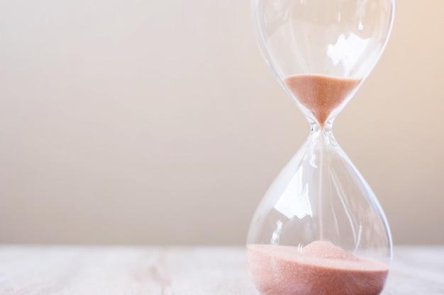 Sablier Sur Table, Sable Coulant à Travers L'ampoule De Sablier Mesurant Le Temps Qui Passe. Compte à Rebours, Délai, Durée De Vie Et Concept De Retraite Photo Premium