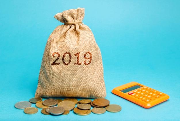 Sac d'argent avec le mot 2019 et une calculatrice. rapport financier d'entreprise. Photo Premium
