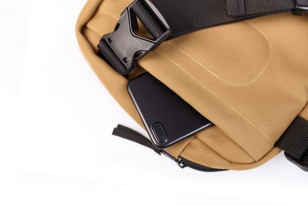 Sac beige sur fond blanc isolé avec une poche cachée pour un téléphone portable se bouchent Photo Premium