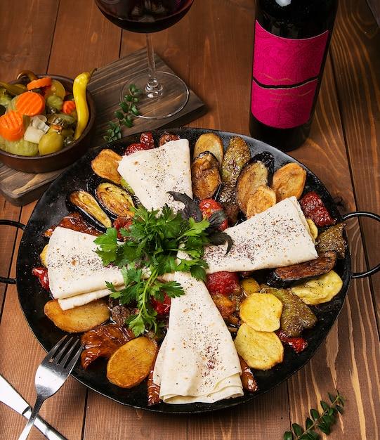 Sac caucasien traditionnel ici avec poulet frit, aubergines, pommes de terre, tomates, courgettes et servi avec lavash, persil, turshu. Photo gratuit