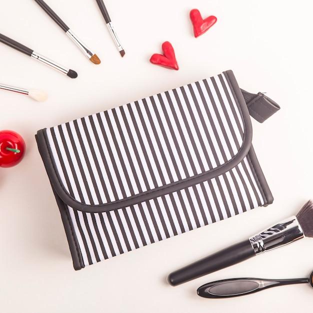 Sac à cosmétiques noir et blanc entre pinceaux de maquillage et choses rouges vives Photo Premium