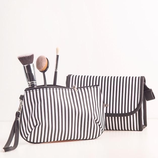 Sac à cosmétiques noir et blanc parmi des pinceaux de maquillage sur fond blanc Photo Premium