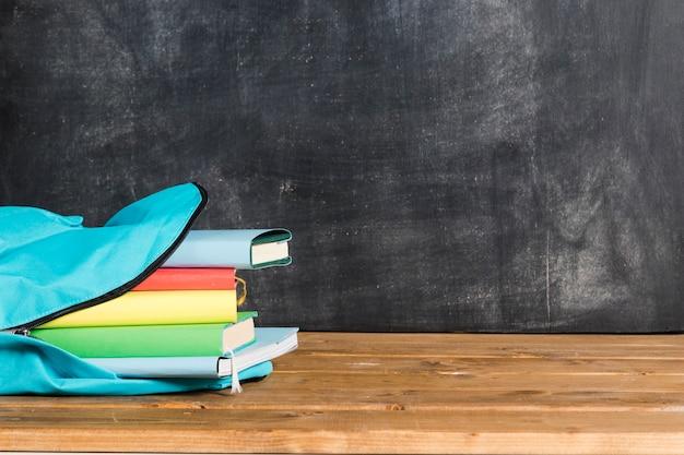Sac à dos bleu avec des livres sur une table en bois Photo gratuit