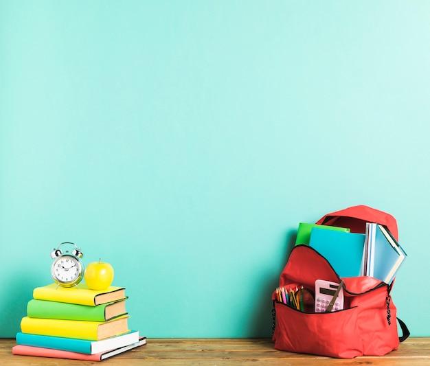 Sac à dos et manuels scolaires sur le bureau Photo gratuit