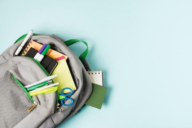 Sac à dos ouvert avec fournitures scolaires Photo gratuit