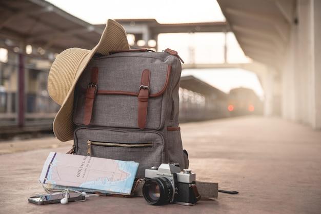Sac à dos, téléphone portable, écouteurs, carte, chapeau et film de caméra sur le sol à la gare Photo Premium