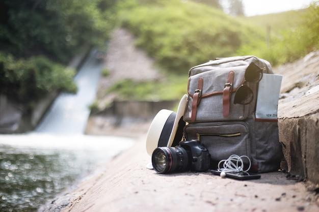 Sac à dos vintage de voyage avec sac, appareil photo, carte, chapeau, écouteurs et téléphone portable sur le sol en été jour eau automne fond. voyage d'aventure . Photo Premium