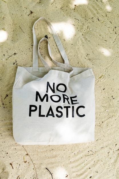 Sac écologique avec signe no more plastic sur le sable de la plage, vue de dessus Photo Premium