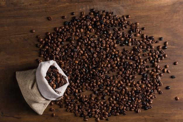Sac avec des grains de café dispersés Photo gratuit