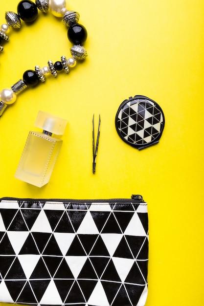 Sac à main femme avec maquillage et accessoires sur surface jaune, Photo Premium