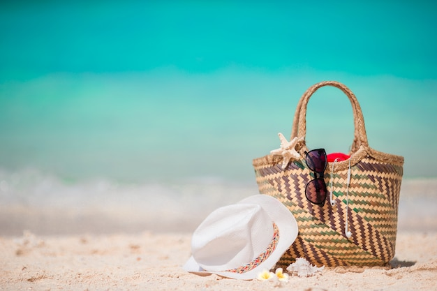 Sac de paille, étoile de poing, casque, chapeau et lunettes de soleil sur la plage blanche Photo Premium