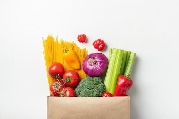 Sac en papier de différents aliments sains sur une table. Photo Premium