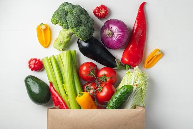 Sac en papier avec des légumes sur fond blanc. Photo Premium