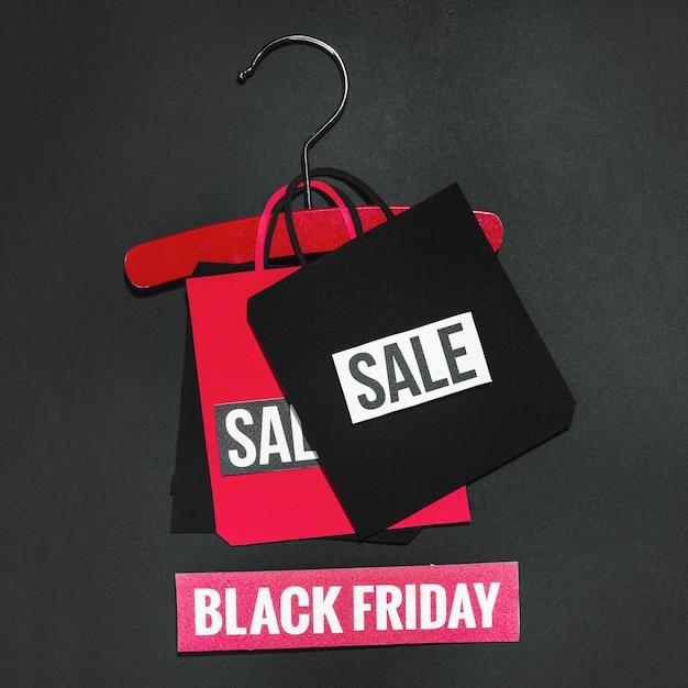 Sac en papier avec signe de vente sur cintre rouge Photo gratuit