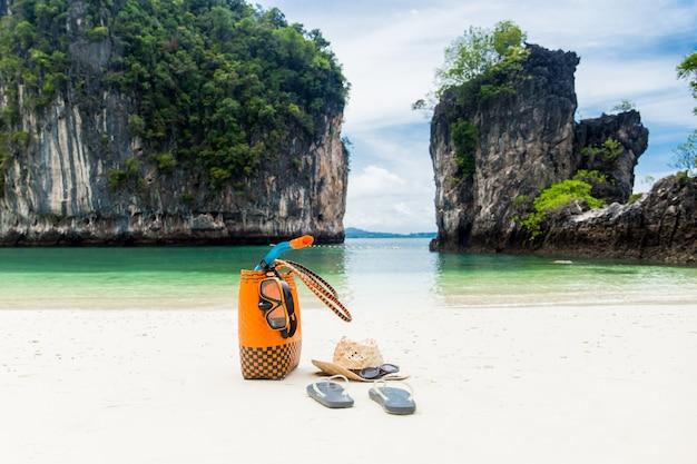 Sac de plage avec accessoires de voyage en vacances d'été. Photo Premium