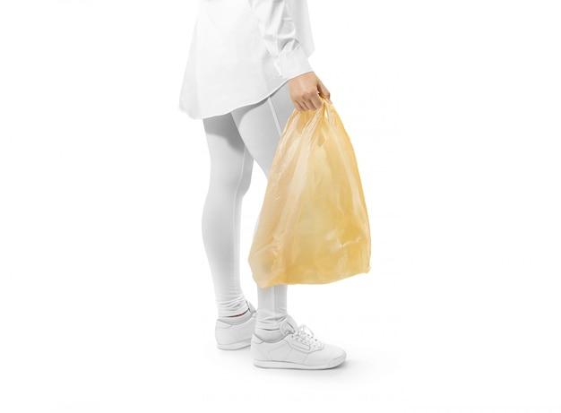 Sac en plastique jaune vierge, tenant la main Photo Premium